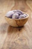Fiołkowi macarons w drewnianym pucharze na drewnianym stole Zdjęcia Royalty Free