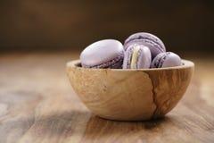 Fiołkowi macarons w drewnianym pucharze na drewnianym stole Zdjęcia Stock