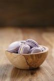 Fiołkowi macarons w drewnianym pucharze na drewnianym stole Obraz Royalty Free