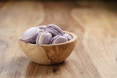 Fiołkowi macarons w drewnianym pucharze na drewnianym stole Zdjęcie Royalty Free
