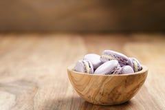 Fiołkowi macarons w drewnianym pucharze na drewnianym stole Zdjęcie Stock