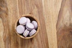 Fiołkowi macarons w drewnianym pucharze na drewnianym stole od above Obrazy Stock
