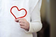 Fio macio vermelho sob a forma do coração em sua menina da mão Imagens de Stock