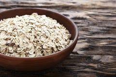 Fiocchi crudi della farina d'avena in un piatto dell'argilla su fondo di legno  immagini stock libere da diritti