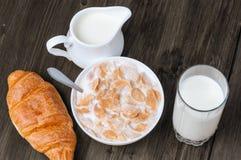 Fiocchi di granturco in ciotola con latte e bicchiere di latte con la brocca sulla vecchia tavola di legno rustica Immagini Stock