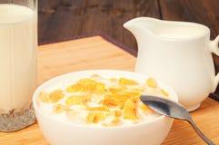 Fiocchi di granturco in ciotola e bicchiere di latte sulla tavola di legno immagine stock