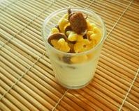 Fiocchi di granturco della prima colazione nel vetro con latte sulla tavola Fotografia Stock