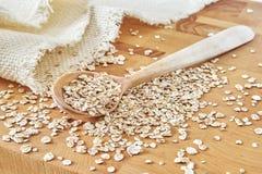 Fiocchi di legno del grano e del cucchiaio sul tagliere Immagine Stock