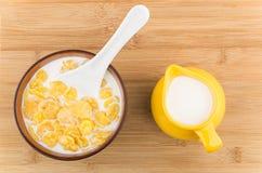 Fiocchi di mais con latte in ciotola e brocca gialla Fotografie Stock Libere da Diritti