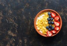 Fiocchi di mais della prima colazione con latte e le bacche fresche, fragole, mirtilli su un fondo scuro Vista superiore, spazio  fotografia stock libera da diritti