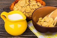 Fiocchi di mais, latte della brocca e ciotola marrone sulla tavola Immagine Stock