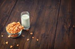 Fiocchi di mais saporiti in ciotola con bicchiere di latte Fotografia Stock Libera da Diritti