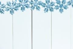Fiocchi di neve blu-chiaro decorati su fondo di legno bianco - con Fotografia Stock