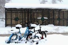Fiocchi di neve che coprono le biciclette durante l'inverno fotografie stock
