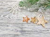 Fiocchi di neve del fondo di Natale, rami del pino e stelle su un fondo di legno immagini stock