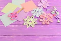 Fiocchi di neve di carta variopinti, strati della carta colorata e residuo, forbici su fondo di legno lilla Immagini Stock Libere da Diritti