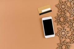 Fiocchi di neve di legno del mestiere, archi, telefono cellulare con lo spazio della copia sullo schermo su fondo beige Fotografia Stock