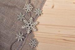 Fiocchi di neve stilizzati su una superficie di legno Fotografia Stock