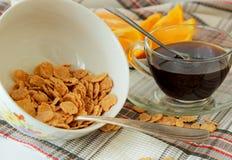 Fiocchi in un piatto, in una tazza di caffè ed in un'arancia profondi, affettati Immagini Stock