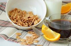 Fiocchi in un piatto, in una tazza di caffè ed in un'arancia profondi, affettati Fotografia Stock Libera da Diritti