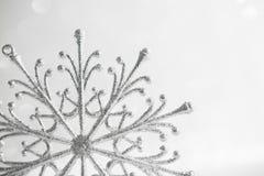 Fiocco di neve d'argento di Natale sul fondo bianco astratto di festa di scintillio Fotografie Stock