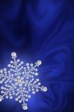 Fiocco di neve del diamante su una seta blu. Fotografia Stock Libera da Diritti