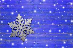 Fiocco di neve del ferro sul bordo di legno blu stagionato Immagine Stock