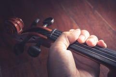 Fiol i violinists hand, filtrerad tappning royaltyfria bilder