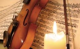 Fiol på musikarket bak en stearinljus Royaltyfri Bild