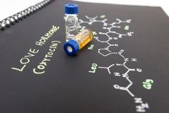 Fiole en gros plan témoin de chapeau bleu sur le carnet avec la formule chimique Photos stock