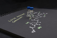 Fiole en gros plan témoin de chapeau bleu sur le papier avec la formule chimique de Images libres de droits