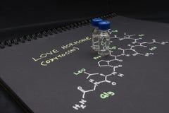 Fiole en gros plan témoin de chapeau bleu sur le papier avec la formule chimique de Photos stock