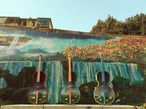 Fioler i gatan och den målade väggen Royaltyfria Bilder