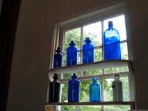 Fioles antiques bleues d'apothicaire sur une étagère de fenêtre Image libre de droits