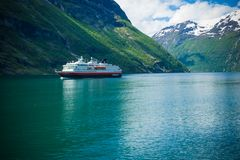 Fiorde de Geiranger, Noruega-JUNHO 15,2012: a balsa Hurtigruten do cruzeiro navega ao longo de Geirangerfjord A viagem foi descri imagem de stock royalty free