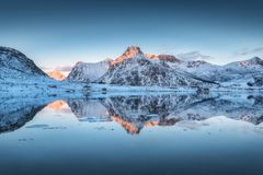 Fiordo con la reflexión en el agua, montañas nevosas en la puesta del sol Fotos de archivo