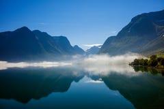 Fiordo in Norvegia con le montagne e la nebbia che appendono sopra l'acqua Fotografia Stock