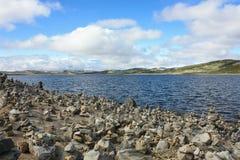 Fiordo, pietre e rocce norvegesi, cielo blu con le nuvole immagini stock