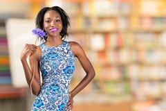 Fiore africano della tenuta della donna immagini stock libere da diritti
