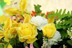 Fiore artificiale giallo e bianco con la foglia verde Fotografia Stock