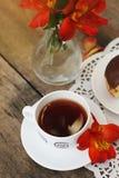 Fiore bianco Alstromeria Astromeria di rosso arancio della ciambella del cioccolato della tazza di tè sopra fondo di legno rustic Immagini Stock Libere da Diritti