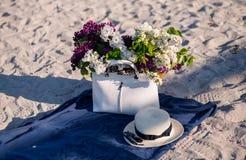 Fiore del lill? Cappello di estate delle donne con un nastro e un mazzo dei fiori lilla su un fondo blu Vista superiore Disposizi immagine stock