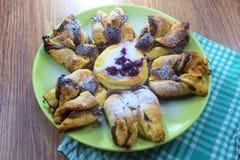 Fiore della pasta sfoglia della pepita del cioccolato con la salsa della vaniglia e l'amarena coperte di zucchero in polvere, di  fotografie stock libere da diritti