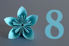 Fiore di carta dagli origami con il numero otto su un fondo grigio 8 marzo, Giornata internazionale della donna Immagini Stock