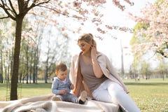 Fiore di ciliegia di Sakura - giovane madre della mamma che si siede con suo figlio del bambino del ragazzino in un parco a Riga, immagine stock libera da diritti