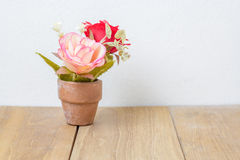 Fiore di plastica in vaso sul bordo di legno Immagine Stock Libera da Diritti