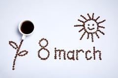 Fiore, il sole e l'iscrizione fatti dai chicchi di caffè fotografia stock