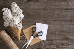 Fiore lilla su fondo di legno rustico con spazio vuoto per il messaggio accogliente Forbici, bobina del filo, piccola busta Immagine Stock