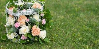 Fiore, rose nell'eleganza misera del birdcage Fondo dell'erba verde Immagine Stock