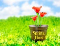 Fiore rosso fatto di vetro in vaso da fiori marrone su erba verde con Immagine Stock Libera da Diritti